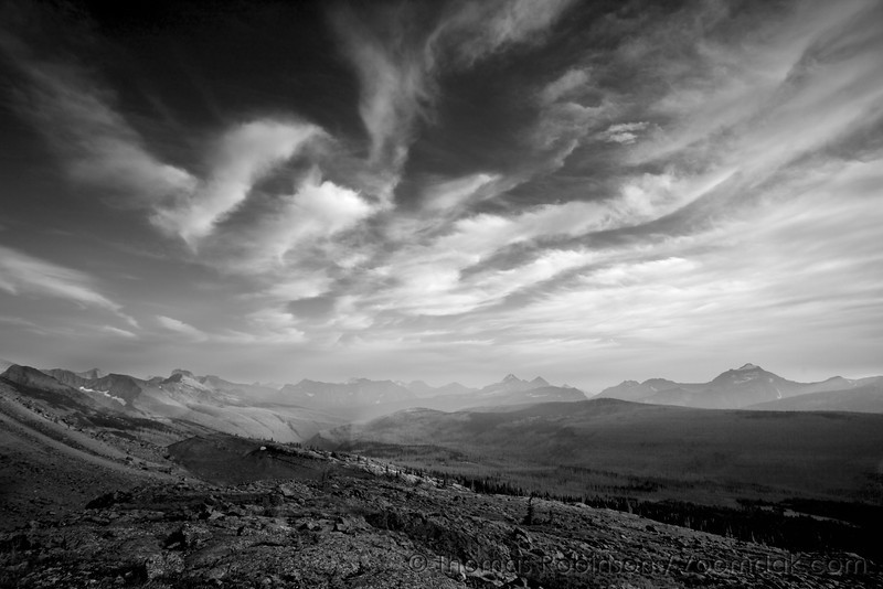 An epic landscape at Fifty Mountain with sweeping clouds and mountains all around. Glacier National Park in Black and White. Glacier is home to 175 mountains.