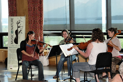 Stringed musicians participating in the music festival in the lobby of the hotel with the Teton Range visible through the windows