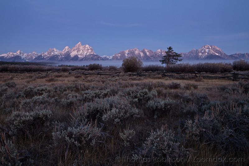 The stretch of the Grand Teton mountains glow before sunrise.