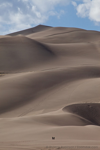 The three people at the bottom of the frame give a sense of scale to the sand dunes at the Great Sand Dunes National Park, Colorado.