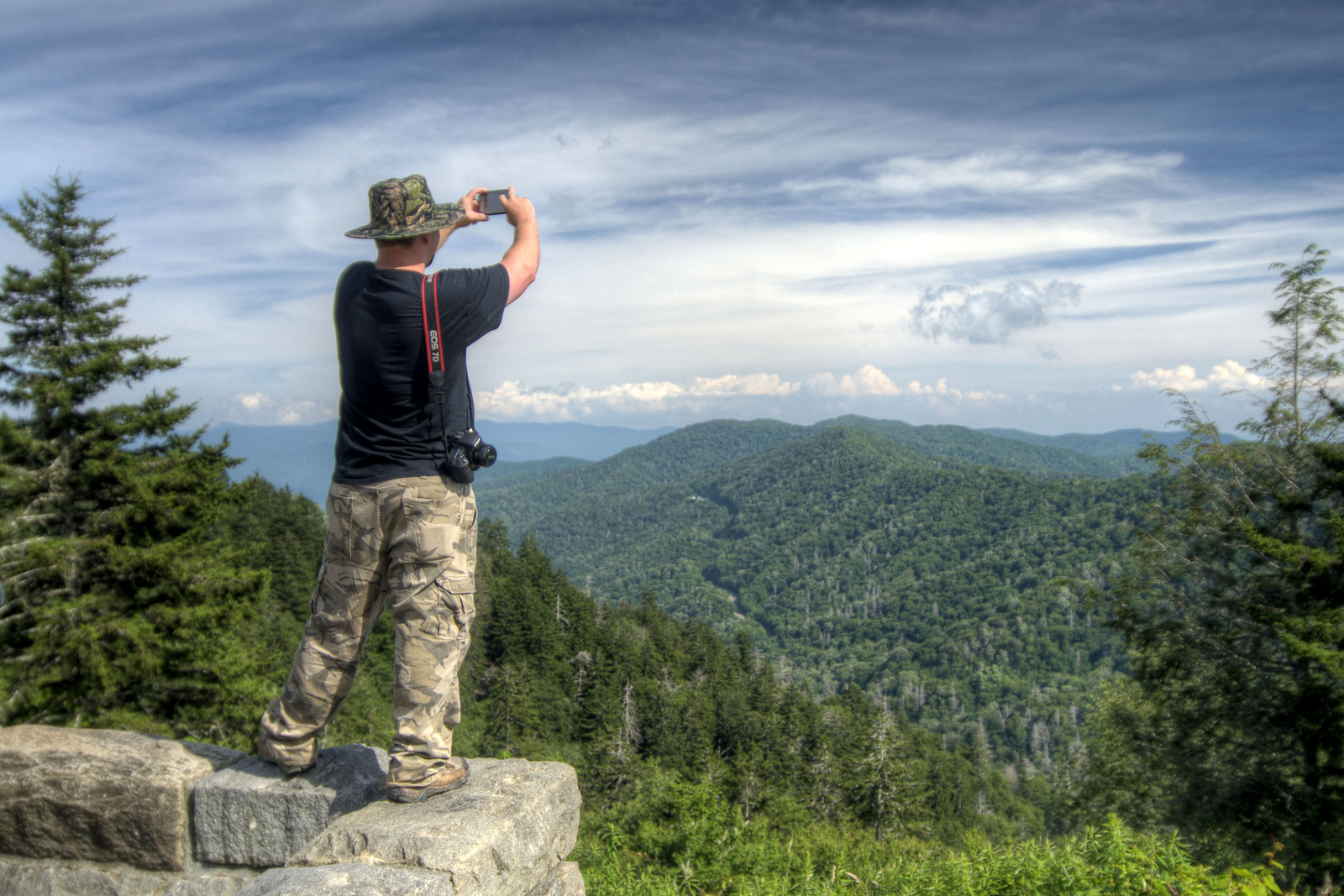 A man stands on top of a stone wall to snap a photo at the Newfound Gap Overlook at the Great Smoky Mountains National Park in Cherokee, NC on Sunday, August 4, 2013. Copyright 2013 Jason Barnette