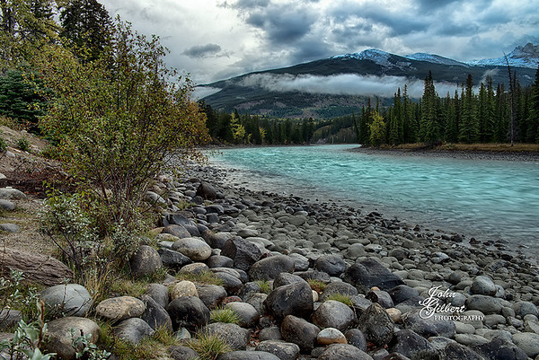 Day 1 (9/30/13) The Athabasca River was just outside our cabin.  Walked to the river to acclimate the camera to the temperature.  It had snowed higher up in the mountains so this made for a good opportunity to get the river with the snow-capped mountains in the background.  Went into town to check out the visitor center and then it was on to the Jasper Tramway.  <br /> <br /> Nikon D600, 24-70mm lens @32mm, Aperture at f/14, Shutter Speed .8 seconds, and ISO 50