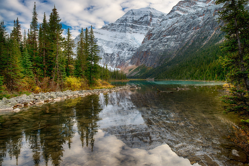 Lake Cavell 10/02/2013:  Mount Edith Cavell is a mountain located in the Athabasca River and Astoria River valleys of Jasper National Park, Canada, and the most prominent peak entirely within Alberta.<br /> <br /> The mountain was named in 1916 for Edith Cavell, an English nurse and executed by the Germans during World War I for having helped allied soldiers escape from occupied Belgium to the Netherlands, in violation of military law. It was previously known as La Montagne de la Grande Traversée (the Mountain of the Great Crossing) because it stands above Athabasca Pass.<br /> <br /> To reach the Edith Cavell access road drive south from Jasper on the Icefields Parkway (highway 93) 5 miles and take the well-marked turnoff onto highway 93A.  Cross the Astoria River and continue 28 kilometers (16 miles) on the mountain road that winds its way to the trailhead.  The road is not suitable for trailers which can be left at the parking lot near the highway.<br /> <br /> Nikon D600, 24-70mm Lens @ 24mm.  Aperture f/8, Shutter Speed 1/40 second, -0.33EV, and ISO 100.  Processed in PS6 using numerous filters and layers.