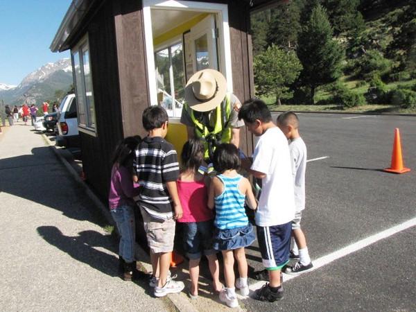 Ranger Ryan gives Jr. Ranger books to visitors