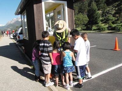 Ranger Ryan gives Jr. Ranger books to visitors