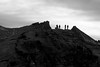 The silhouette of hikers at the summit of Lembert Dome at 9,450 ft (2,880 m) in Yosemite National Park. Cathedral Peak visible in the background.