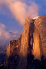 A cloud catches the sunset color while resting upon the top of Half Dome at sunset from Glacier Point in Yosemite National Park.