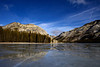 Polly Dome reflects off the frozen Tenaya Lake along Tioga Road in Yosemite National Park.