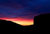 The cliff of El Capitan stands silhouetted against the afterglow of a vibrant sunset.