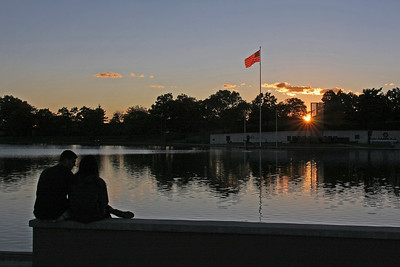 A couple enjoys the sunset by the 9-11 Memorial in Eisenhower Park