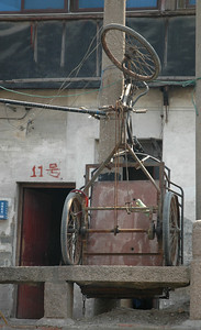 Upright tricycle tied to pole.  These vehicles are an importnat mode of transporting goods for poorer Chinese merchants - Suzhou, China  ©Gerald Diamond All rights reserved