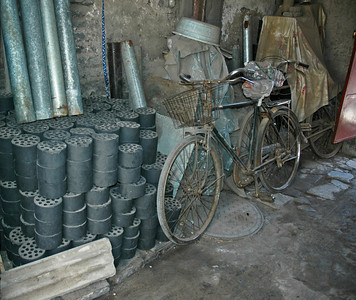 Bicycles and Coal. In the Beijing hutongs (ancient downtown neighbourhoods) these two items plainly tell one side of the story of China's developing economy.  For many the main source of home heating and cooking is still heavily polluting coal and the main mode of transport is the more environmentally friendly bicycle. But both are practical and cheap.  Beijing, China.  ©Gerald Diamond All rights reserved
