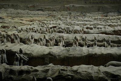 Row upon row of make-believe soldiers peer intently from their clay trenches in Xian's gloomy Pit #1 where thousands of terra cotta warriors stand guard for their long past Emperor and Master.  ©Gerald Diamond All rights reserved
