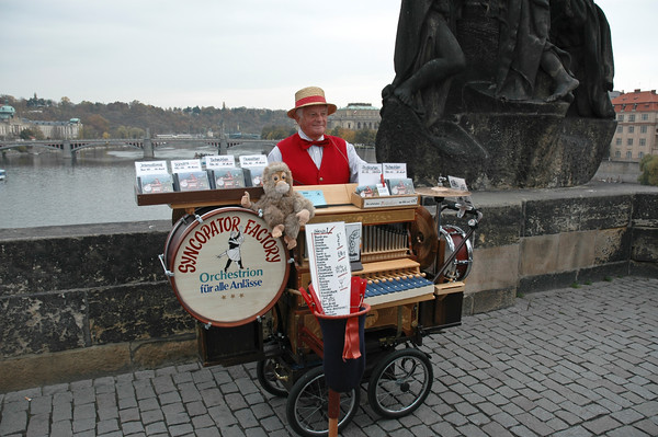 """The Monkey Died.  On Charles Bridge in Prague, overlooking the Vltava River, this """"organ grinder"""" now is accompanied by a stuffed monkey.  ©Gerald Diamond All rights reserved"""