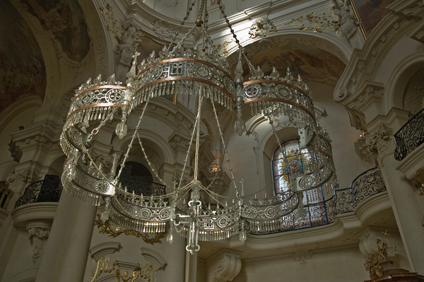 Bold church chandelier against white walls, gilded arches and ornate ironwork balconies. Prague, Czech Republic  ©Gerald Diamond All rights reserved