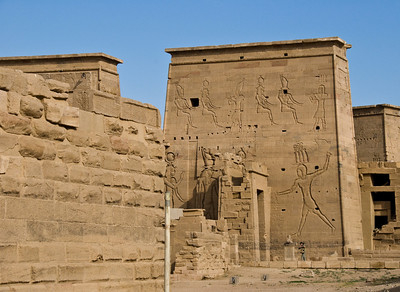 The Temple of Philae with its huge walls (see the woman at the base of the wall for scale) provides a beautiful tableau for hieroglyphs and images of the Gods and Pharaohs.  This Temple is more than 2,000 years old and still standing on an island in the Nile River.  ©Gerald Diamond All rights reserved