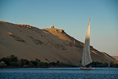 Faluccas (small sailing vessels) glide along the Nile near Luxor under the hilltop memorial to a local prominent citizen.  ©Gerald Diamond All Rights Reserved