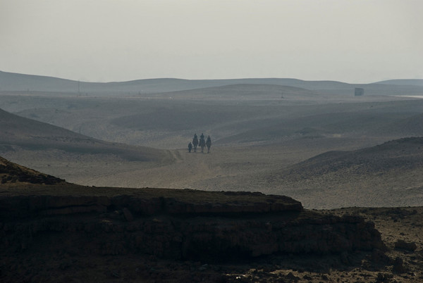 Lonely travelers on foot and camel in the desert west of Cairo on the great Giza plain.  ©Gerald Diamond All rights reserved