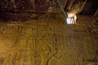 An inner sanctum of Karnak Temple lit only by a high window casting an oblique light on the intricately decorated walls and ceiling of the room.  ©Gerald Diamond All rights reserved