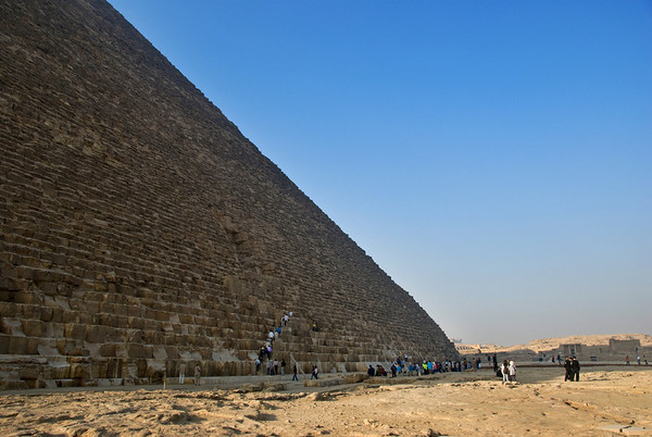 The Great Pyramid at Giza - People ascending to a small opening a few tiers up from the base.  The sheer mountainous immensity of the pyramid is daunting when seen in person.  ©Gerald Diamond All rights reserved