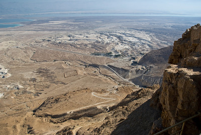 Masada - From the top one can see the footpath that snakes down to the base of the mountain over 1,000 feet below.  The path was originally built by the Romans almost 2,000 years ago.  Looking carefully you can see the remains of the square encampment walls erected by the Romans during the 18-month siege of Masada.  In the distance is the Dead Sea.  ©Gerald Diamond All rights reserved