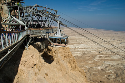 Masada cable car suspended over the abyss with the desert below and the Dead Sea in the distance.  ©Gerald Diamond All rights reserved