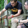 A staff member from Hemlocks helps a camper with archery.