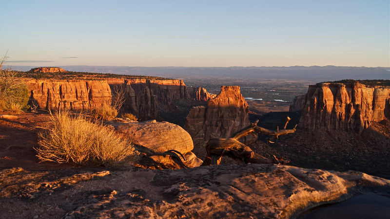 First rays of morning sun light Independence Monument and surrounding cliffs; Colorado National Monument