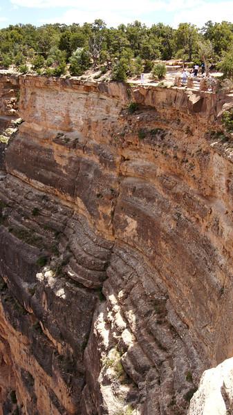A tourist (in white) chooses a precarious viewing spot; Grand Canyon, Arizona.