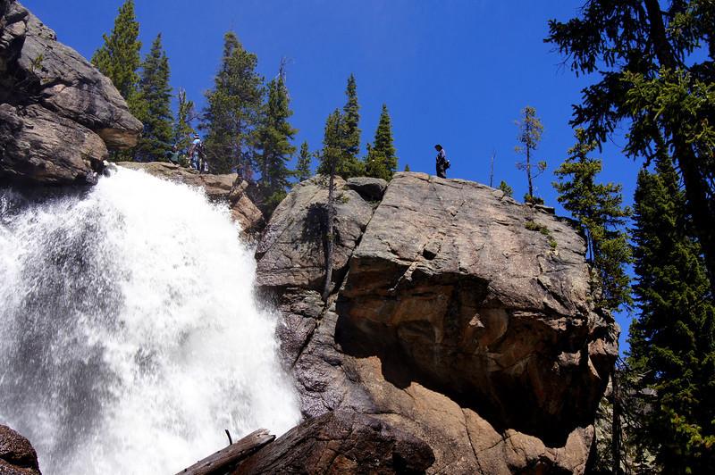 Hikers on the rocks above Ouzel Falls, Rocky Mountain National Park, Colorado.
