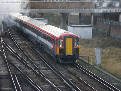 A Gatwick Express passes through the steam from a VSOE working