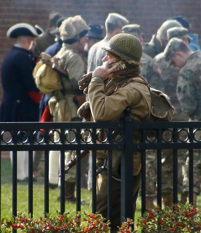 . A World-War II army re-enactor leans on a fence as other re-enactors representing military from the French-Indian War, and Civil War mingle with current service men and women as part of the Steel City Supports the Troops event to honor Veterans Day at Point State Park in Pittsburgh, Saturday, Nov. 11, 2017. (AP Photo/Keith Srakocic)