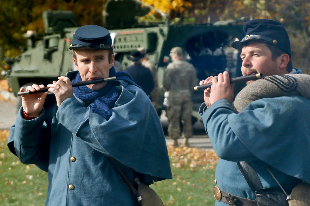 . Civil War re-enactors Brian Steffey, left, and Craig Anderton play fifes while wearing Civil War era Union Army uniforms near a current Army armored personnel carrier on display as part of the Steel City Supports the Troops event to honor Veterans Day at Point State Park in Pittsburgh, Saturday, Nov. 11, 2017. (AP Photo/Keith Srakocic)