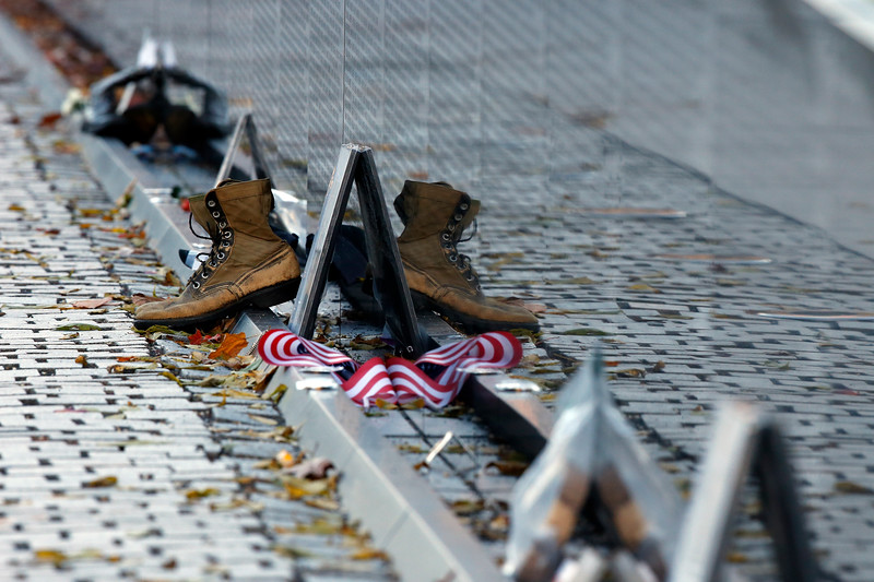 Mementos including a worn pair of boots, have been replaced after the wall was cleaned at the Vietnam Veterans Memorial on Veterans Day, Saturday, Nov. 11, 2017 in Washington. (AP Photo/Alex Brandon)