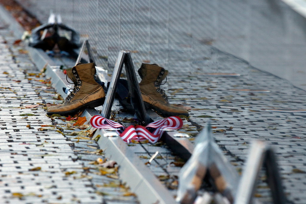. Mementos including a worn pair of boots, have been replaced after the wall was cleaned at the Vietnam Veterans Memorial on Veterans Day, Saturday, Nov. 11, 2017 in Washington. (AP Photo/Alex Brandon)