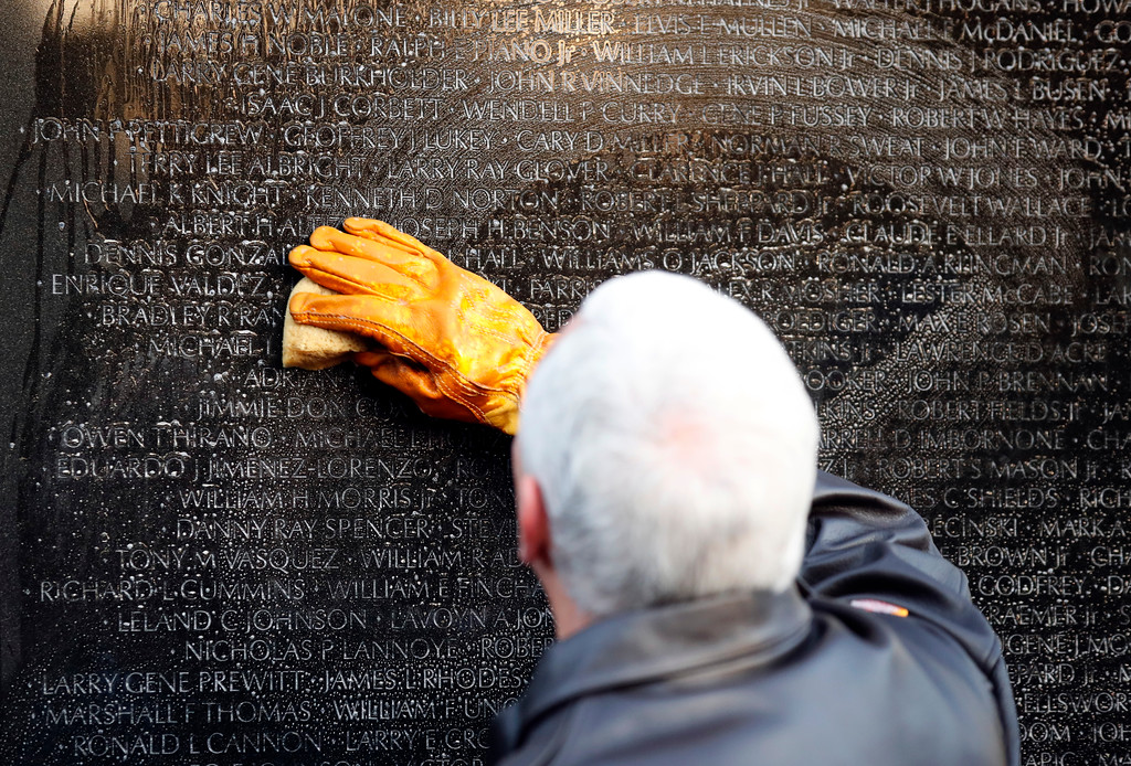 . Vice President Mike Pence cleans a portion of the wall at the Vietnam Veterans Memorial on Veterans Day, Saturday, Nov. 11, 2017 in Washington. (AP Photo/Alex Brandon)