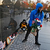 Volunteers remove mementos before cleaning the wall at the Vietnam Veterans Memorial on Veterans Day, Saturday, Nov. 11, 2017 in Washington. (AP Photo/Alex Brandon)