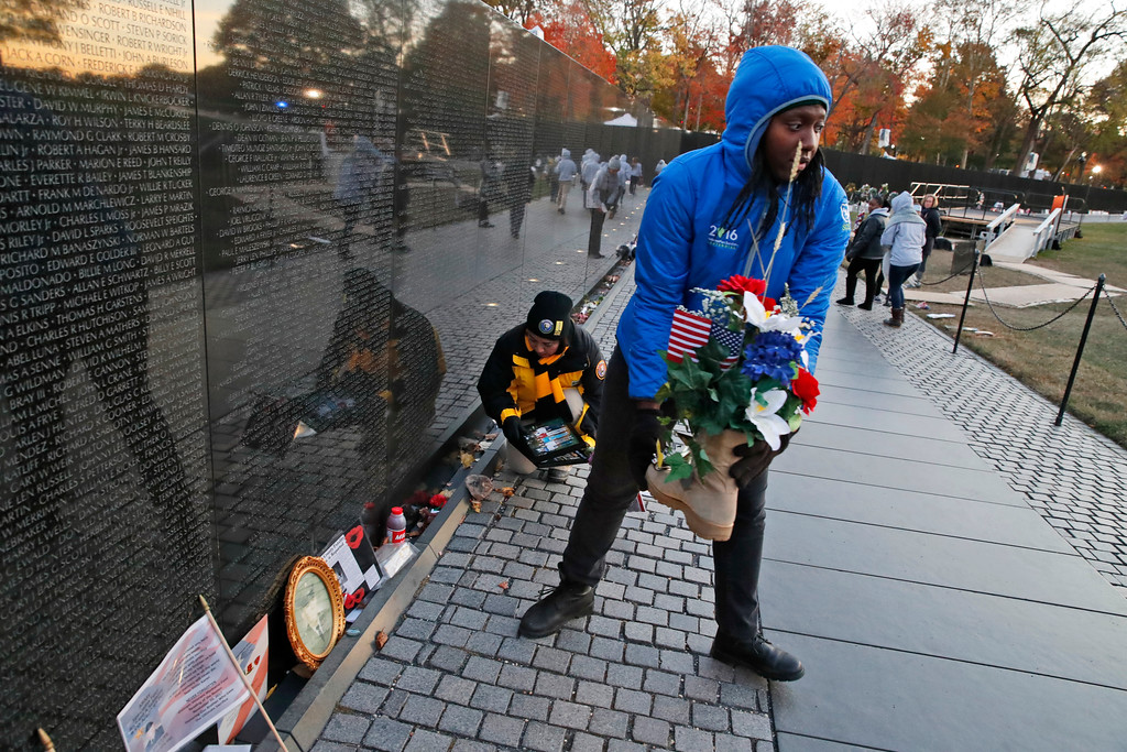 . Volunteers remove mementos before cleaning the wall at the Vietnam Veterans Memorial on Veterans Day, Saturday, Nov. 11, 2017 in Washington. (AP Photo/Alex Brandon)