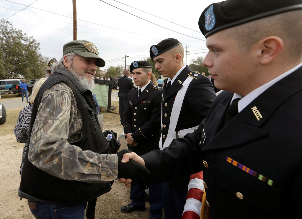 . Veteran and Sutherland Springs First Baptist Church member Ted Montgomery, left, greets members of the St. Mary\'s ROTC following a Veterans Day event, Saturday, Nov. 11, 2017, in Sutherland Springs, Texas. A man opened fire inside the church in the small South Texas community on Sunday, killing more than two dozen. (AP Photo/Eric Gay)