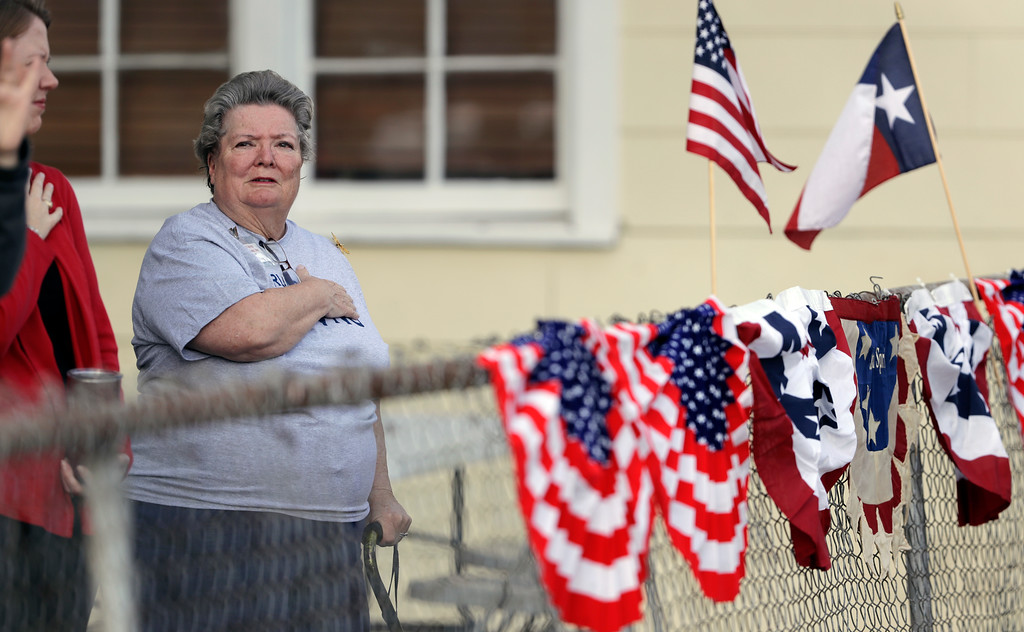 . Donna King stands for the national anthem during a Veterans Day event, Saturday, Nov. 11, 2017, in Sutherland Springs, Texas. The event was held in the community, just a block away from the Sutherland Springs First Baptist Church where a man opened killing more than two dozen. Veteran Robert Corrigan, who was killed in the church, was honored during the service. (AP Photo/Eric Gay)