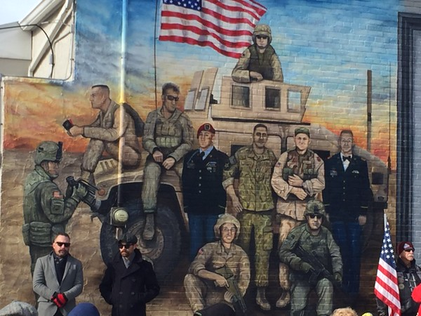 . Kevin Martin�The Morning Journal <br> Amherst artists Brian Goodwin and Mike Sekletar stand in front of their newly unveiled mural in dedication to Lorain County veterans of Iraq and Afghanistan on Nov. 11 during Amerherst\'s Veteran\'s Day celebrations at 248 Park Ave.. The mural depicts ten fallen U.S. servicemen after Sekletar and Goodwin worked with families to paint their likenesses