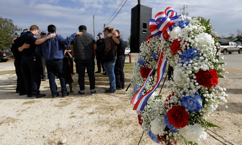 . First responders join in prayer following a Veterans Day event, Saturday, Nov. 11, 2017,  near the Sutherland Springs First Baptist Church, in Sutherland Springs, Texas. A man opened fire inside the church in the small South Texas community on Sunday, killing more than two dozen. (AP Photo/Eric Gay)