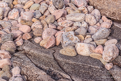 Contrasting textures of rugged granite and wave polished stones on the Georgian Bay shoreline, Parry Sound, Ontario, Canada