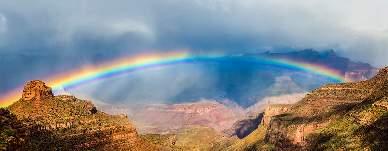 A beautiful rainbow arcs over the Grand Canyon.