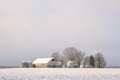 A small farm in rural indiana in winter. The sky is mostly cloudy