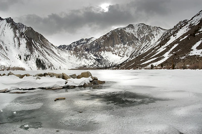 Winter scenery. Frozen lake surrounded by a mountain range in a dark stormy weather. Convict Lake. Mammoth, California.