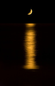 Spooky moonset at night, orange golden colors, setting over the ocean. Long beautiful reflection on water.