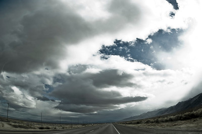 Wide angle shot of a highway in the desert  with contrasting high clouds.