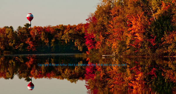 Elcho water tower and autumn gorgeous orange reflections under blue skies over Otter Lake within northeastern Wisconsin and the wolf River watershed (USA WI Elcho)