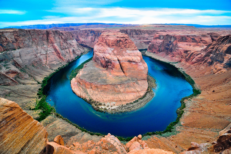 Upon reaching the overlook, one is awed by the magnificence of the landscape that cannot be expressed in words or through a photograph. The overlook is at the top of a steep orange colored cliff several hundreds of feet high. Down below, an emerald green Colorado river makes a horse-shoe shaped bend before rushing towards the Grand Canyon.